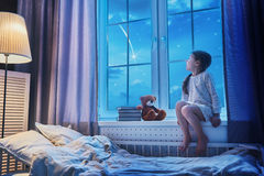 De zitting van het meisje bij het venster Royalty-vrije Stock Foto's