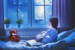 De zitting van het meisje bij het venster Stock Afbeeldingen