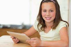 De zitting van het meisje bij keukenlijst met tablet Stock Foto's