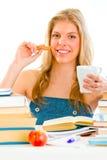 De zitting van het meisje bij lijst met boeken en het drinken thee Royalty-vrije Stock Foto