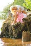 De zitting van het meisje bij rivierbank met hoofd op haar knieën stock foto's