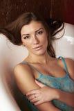 De zitting van het meisje in de badkamers in marine bluethe bad Royalty-vrije Stock Afbeeldingen