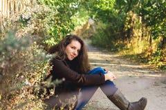 De zitting van het meisje in de herfstpark stock fotografie