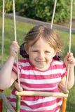De zitting van het meisje in de tuin in de zomer. Royalty-vrije Stock Foto's