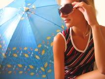 De zitting van het meisje dichtbij een paraplu Stock Foto