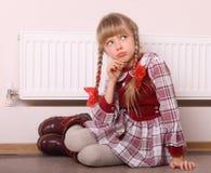 De zitting van het meisje dichtbij radiator. De depressie van de warmte. Stock Foto's