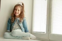 De zitting van het meisje door het venster royalty-vrije stock afbeeldingen
