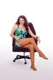 De zitting van het meisje in een leunstoel Stock Afbeeldingen