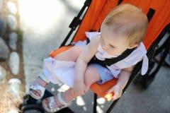 De zitting van het meisje in een wandelwagen Stock Foto