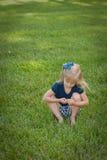 De zitting van het meisje in gras Royalty-vrije Stock Afbeelding