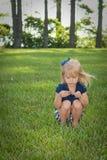 De zitting van het meisje in gras Royalty-vrije Stock Foto
