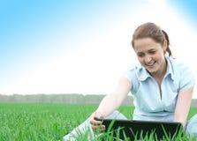 De zitting van het meisje in het gras Stock Afbeelding