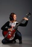 De zitting van het meisje met basgitaar en spelmuziek Royalty-vrije Stock Foto