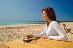 De zitting van het meisje met glazen op een strand Stock Afbeeldingen
