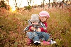 De Zitting van het meisje met Haar Broer van de Baby op een Gebied stock foto
