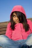 De zitting van het meisje op de bank Stock Foto