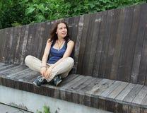 De zitting van het meisje op de bank Royalty-vrije Stock Foto
