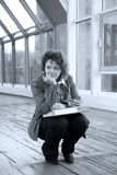 De zitting van het meisje op de brug Stock Foto