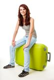 De zitting van het meisje op de grote groene bagagezak Stock Foto