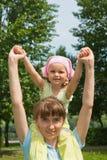 De zitting van het meisje op de hals van haar moeder Royalty-vrije Stock Fotografie