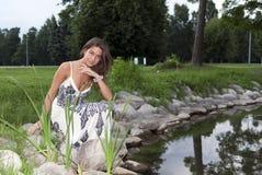 De zitting van het meisje op de rand van de vijver Royalty-vrije Stock Foto's