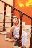 De zitting van het meisje op de treden Stock Foto