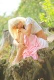 De zitting van het meisje op een aard met hand op knieën stock afbeelding