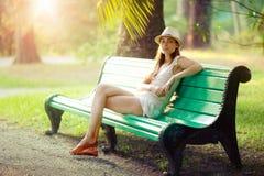 De zitting van het meisje op een bank Stock Foto's
