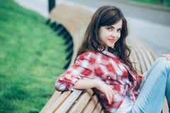 De zitting van het meisje op een bank royalty-vrije stock foto