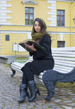 De zitting van het meisje op een bank en lezing een boek Royalty-vrije Stock Fotografie