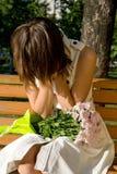 De zitting van het meisje op een bank in park het schreeuwen stock afbeelding