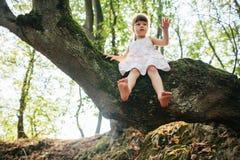 De zitting van het meisje op een boom voeten Stock Afbeeldingen