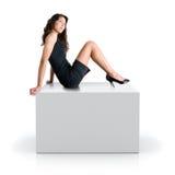 De zitting van het meisje op een grijze kubus Royalty-vrije Stock Afbeeldingen