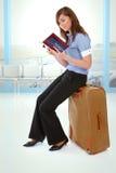 De zitting van het meisje op een koffer Stock Fotografie