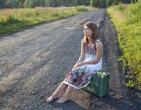 De zitting van het meisje op een koffer op de kant van de weg Royalty-vrije Stock Foto's