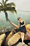 De zitting van het meisje op een kokospalm stock fotografie
