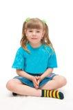 De zitting van het meisje op een lichte achtergrond Royalty-vrije Stock Fotografie