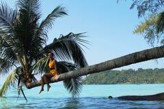 De zitting van het meisje op een palm Stock Foto