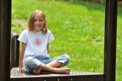 De Zitting van het meisje op een Speelplaats royalty-vrije stock fotografie