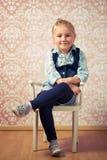 De zitting van het meisje op een stoel Stock Foto