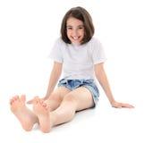 De zitting van het meisje op een vloer stock afbeelding
