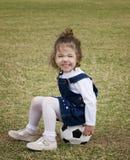 De zitting van het meisje op een voetbalbal. Royalty-vrije Stock Afbeeldingen