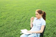De zitting van het meisje op het gebied Stock Foto