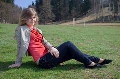 De zitting van het meisje op het gras Stock Afbeeldingen