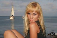 De zitting van het meisje op het strand Stock Fotografie