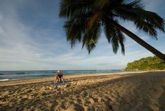 De zitting van het meisje op het strand Stock Afbeeldingen