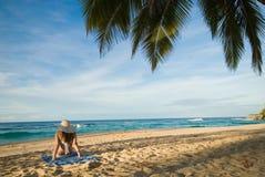 De zitting van het meisje op het strand Stock Foto's