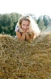 De zitting van het meisje op hooi Royalty-vrije Stock Fotografie