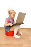 De zitting van het meisje op rode onbenullig met computer Stock Afbeelding