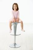 De zitting van het meisje op stoel Stock Foto's